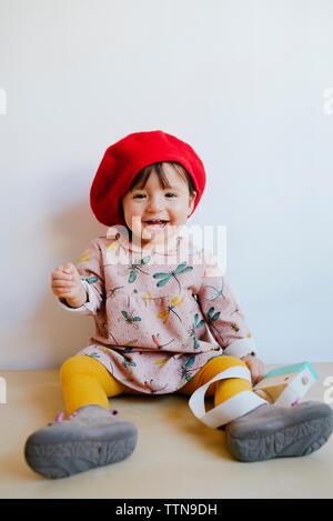 Portrait von fröhlichen Mädchen tragen von Red Hat auf dem Boden gegen die Wand zu Hause sitzen - Stockfoto