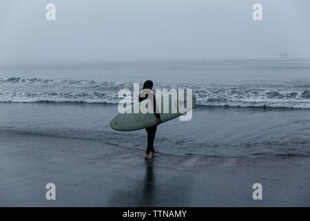 Ansicht der Rückseite Frau mit Surfbrett zu Fuß am Strand gegen Sky - Stockfoto