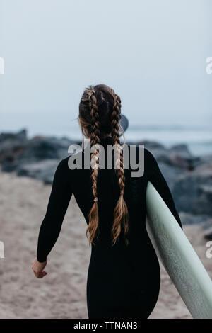 Ansicht der Rückseite Frau mit geflochtenem Haar, Surfbrett beim Spaziergang am Strand gegen Sky - Stockfoto