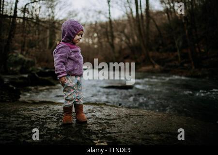 Kleinkind auf Felsen über Fluss im Winter - Stockfoto
