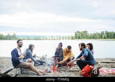 Gerne Freunde braten Würstchen am Lagerfeuer am Ufer gegen Sky - Stockfoto