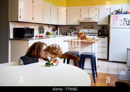 Mutter spielt mit Sohn in der Küche zu Hause. - Stockfoto