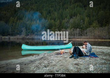 Volle Länge des Paar ruhen von Lagerfeuer am Seeufer im Silver Lake Provincial Park - Stockfoto