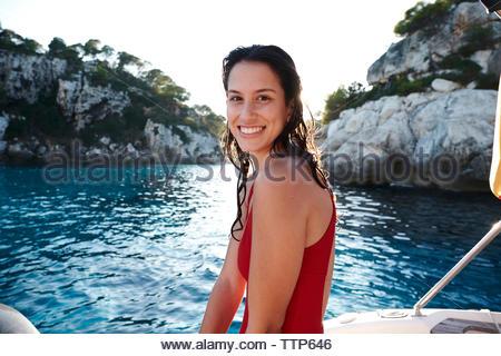 Porträt der Frau in Badehosen sitzen auf Boot gegen klaren Himmel bei Sonnenuntergang - Stockfoto