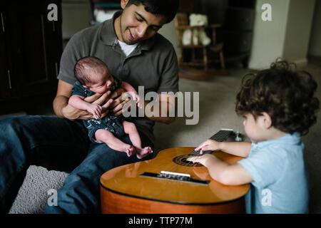 Baby Boy, Gitarre zu spielen, während Sie von Vater und Kind Bruder zu Hause sitzen - Stockfoto