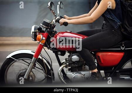 Niedrige Abschnitt von Frau reiten Motorrad auf der Straße - Stockfoto