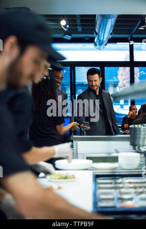 Unternehmer zahlen Rechnung durch Smart Phone beim stehen im Restaurant - Stockfoto