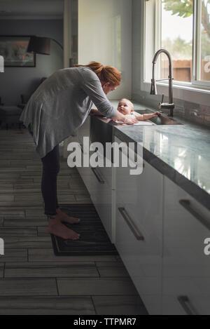 Seitenansicht von Mutter Baden niedlichen Sohn in der Küche zu Hause. - Stockfoto