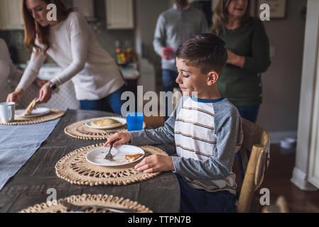 Junge Pfannkuchen essen für Frühstück
