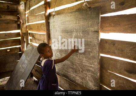 Seitliche Sicht auf Mädchen schreiben auf Tafel im Klassenzimmer - Stockfoto