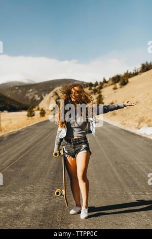 Unbeschwerte junge Frau mit Skateboard stehend auf der Straße während der sonnigen Tag - Stockfoto