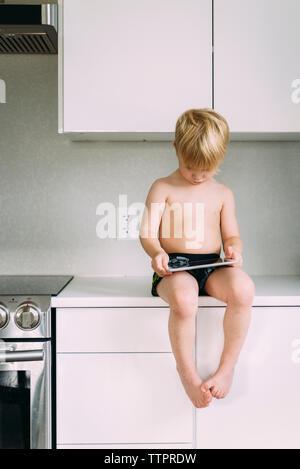 Shirtless Boy mit Tablet Computer, während auf der Arbeitsplatte in der Küche zu Hause sitzen - Stockfoto