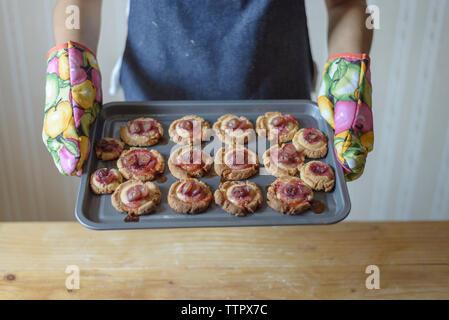 Mittelteil der Frau mit Backblech mit Cookies bei der Tabelle in Home - Stockfoto