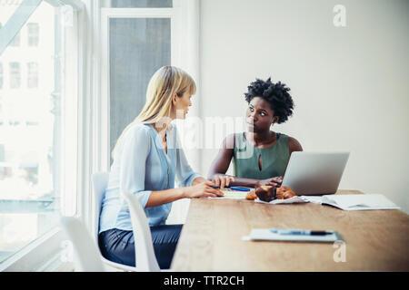 Junge Unternehmerinnen am Konferenztisch in der kreativen Büro - Stockfoto