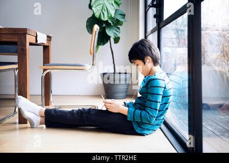 Junge mit digitalen Tablet beim Sitzen durch Fenster - Stockfoto