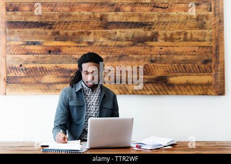 Junge Unternehmer schriftlich auf Papier während der Arbeit am Laptop im Büro - Stockfoto