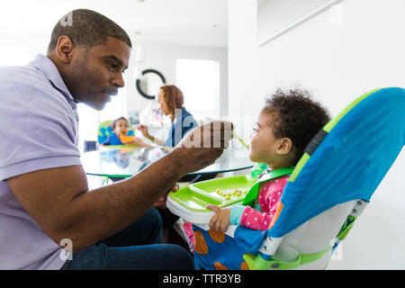 Die Eltern füttern Töchter während am Tisch sitzen - Stockfoto