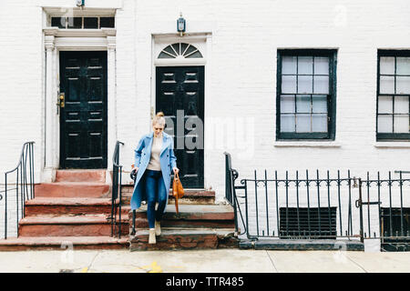 Volle Länge des jungen Frau gehen, Schritte der Wohngebäude - Stockfoto