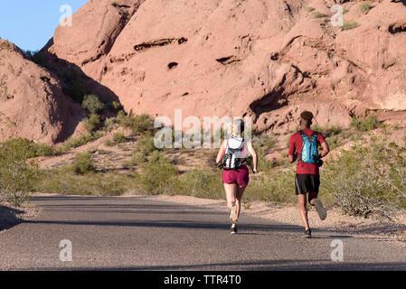 Ansicht der Rückseite des Wanderer mit Rucksäcken, die auf der Straße gegen Felsformationen während der sonnigen Tag - Stockfoto