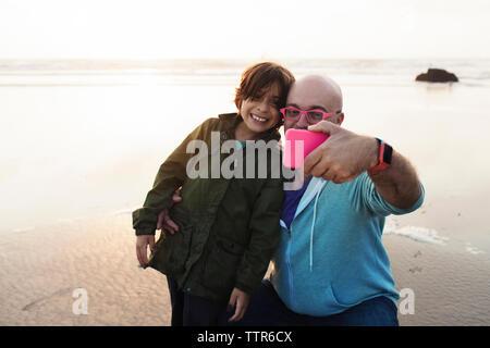 Vater und Sohn selfie mit Smart Phone am Strand - Stockfoto