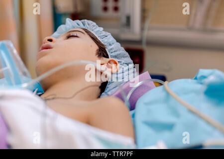 Seitenansicht der Junge liegend auf Bett schlafen im Krankenhaus nach der Operation. Stockfoto