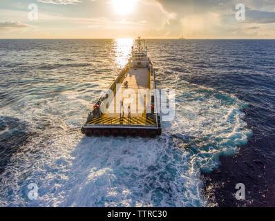 Hohe Betrachtungswinkel der Arbeiter auf Container schiff Segeln im Meer bei Sonnenuntergang