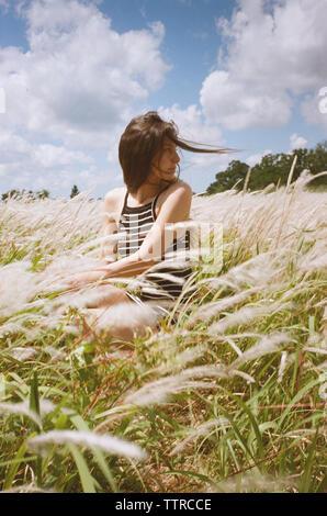Frau sitzt auf Feld gegen Sky bei windigem Wetter - Stockfoto