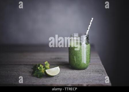 Gesunden grünen Smoothie im Marmeladenglas mit Kalk auf Tisch - Stockfoto