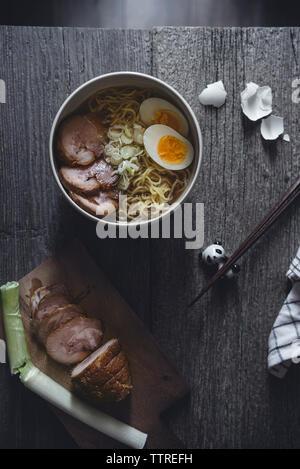 Ansicht von oben von char sui Schweinefleisch und Ramen Nudeln mit Ei auf hölzernen Tisch - Stockfoto