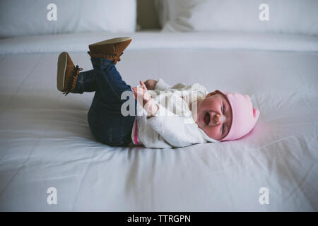 Fröhliches Baby lacht, während am Bett zu Hause liegen - Stockfoto