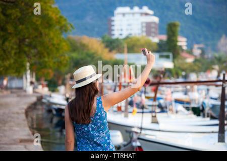 Ansicht der Rückseite Frau mit Hut unter selfie beim Stehen am Hafen in der Stadt