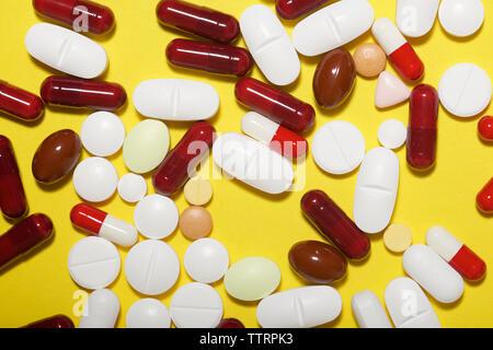 Hohe Betrachtungswinkel verschiedener Medikamente auf gelbem Hintergrund - Stockfoto