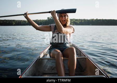 Portrait von Frau mit Mund offen halten oar beim Sitzen im Boot auf dem Fluss gegen Sky Stockfoto
