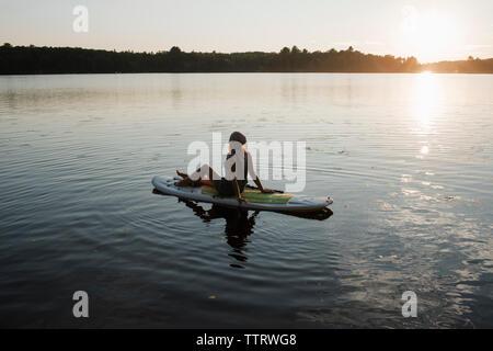 Seitenansicht der Frau sitzt auf der paddleboard am Fluss gegen Himmel bei Sonnenuntergang - Stockfoto