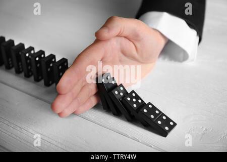 Männliche Hand anhalten domino Effekt auf hölzernen Tisch - Stockfoto