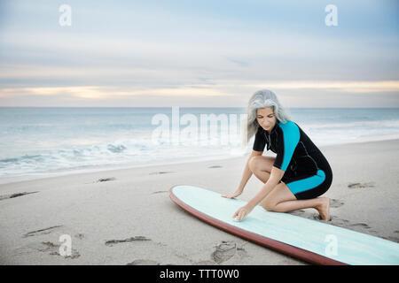 Weibliche surfer Reinigung Surfbrett am Delray Strand bei Sonnenuntergang - Stockfoto