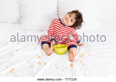 Lächelnde Junge auf weißen Bett und Verwirrung mit Müsli Schale - Stockfoto
