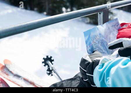 Zugeschnittenes Bild von Mädchen auf Karte suchen, beim Reiten auf Skilift - Stockfoto