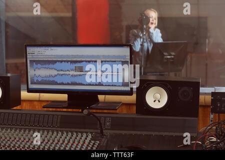 Junge Frau mit der Aufnahme eines Songs in einem professionellen Studio. Blick vom Sound Engineer Arbeitsplatz - Stockfoto