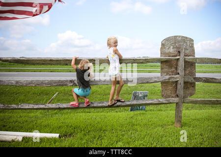 Zwei Mädchen hängen auf hölzernen Zaun auf der Farm - Stockfoto