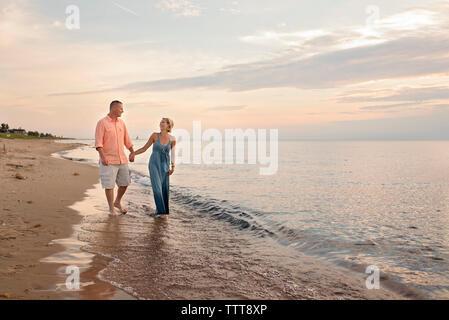 Paar Hände halten beim Gehen auf Ufer am Strand bei Sonnenuntergang - Stockfoto