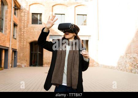 Junge Frau mit einem VR-Headset im Freien - Stockfoto