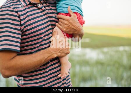 Mittelteil der Vater die Jungen beim Stehen im Feld - Stockfoto