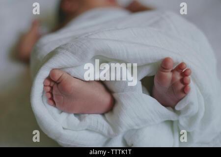Untere Partie der Baby in Blatt liegend auf Bett - Stockfoto