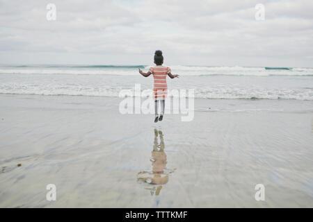 Ansicht der Rückseite des Mädchen springen am Strand - Stockfoto
