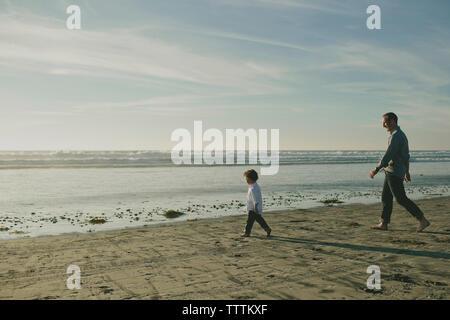 Seitenansicht von Sohn und Vater zu Fuß am Strand gegen Himmel während der sonnigen Tag - Stockfoto