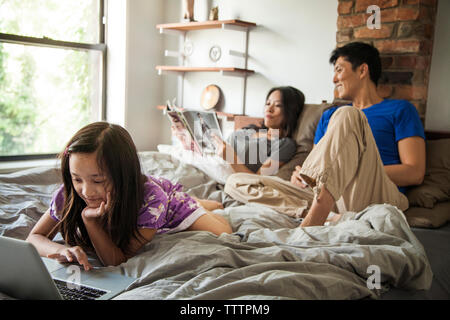 Mädchen mit Laptop und Entspannen mit Eltern am Bett zu Hause - Stockfoto