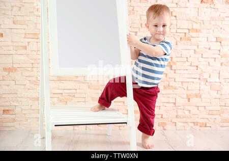 Stilvolle baby boy in einem gestreiften T-Shirt in der Nähe der Spiegel posiert - Stockfoto