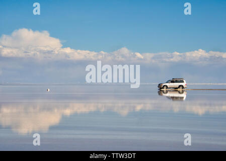 Jeep fahren auf der reflektierten Fläche der Salzsee, Salar de Uyuni, Potosi, Bolivien - Stockfoto