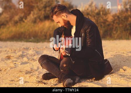 Stattlicher Mann mit Gitarre am Strand - Stockfoto